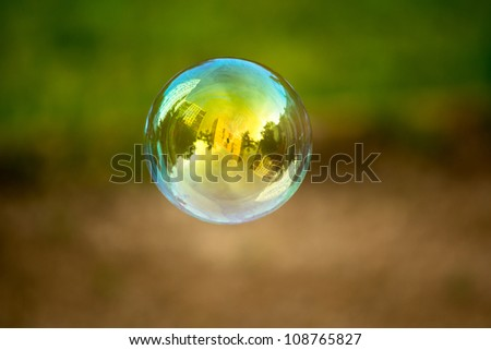 Soap bubble flying. Houses reflected in. - stock photo