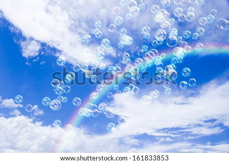 Soap bubbles in the cloudy sky with rainbow - stock photo
