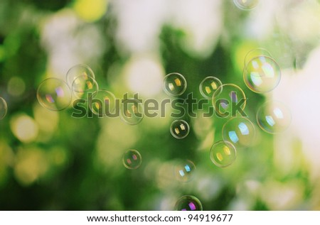 Soap bubbles on green background - stock photo