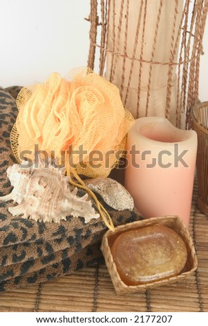 Soap, candle, sponge, sea shells and leopard towels on bamboo mat - stock photo