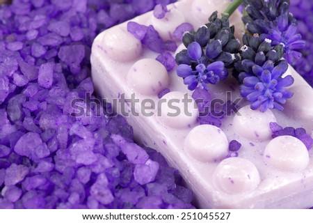 Soap in heap of violet bath salt close-up. - stock photo