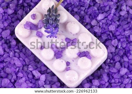 Soap in heap of violet bath salt. Top view. - stock photo