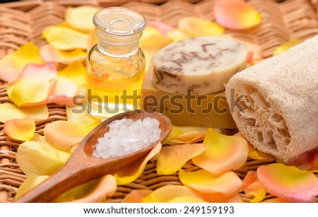 soap with rose petals ,salt in spoon ,oil on bamboo mat - stock photo