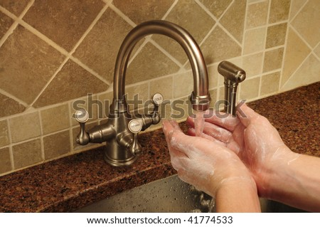 Soapy hand washing under flowing water out of a kitchen faucet - stock photo