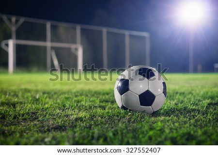 Soccer at night. Classical football on the playground, reflector made a beautiful lens flare in the background - stock photo