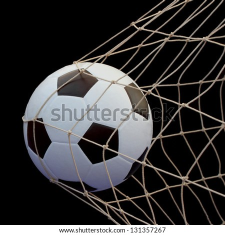 Soccer ball flying in the net isolated on Black background - stock photo