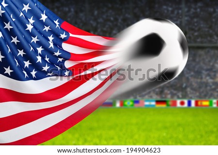 Soccer ball in fast motion in front of the American flag waving in a spiffy way in a crowded arena - stock photo