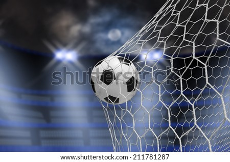 soccer ball in goal at night - stock photo