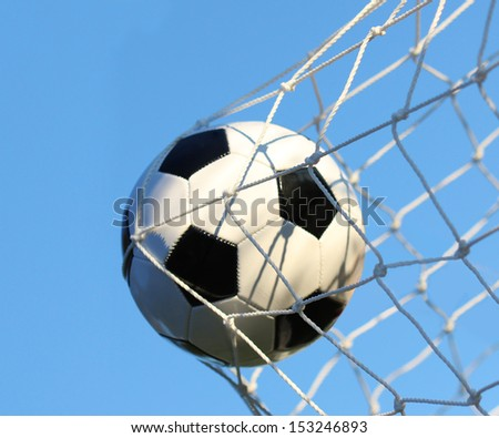 Soccer ball in goal net over blue sky. Football. Victory - stock photo