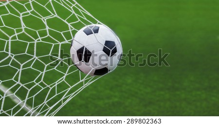 soccer ball in goal with green backgroung - stock photo