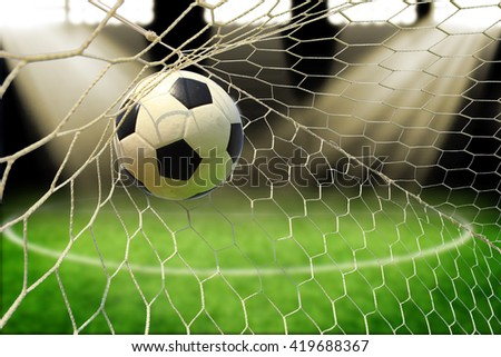 soccer ball in goal with spotlight - stock photo