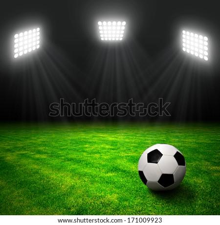 Soccer ball in grass, soccer stadium with the dright lights.  - stock photo