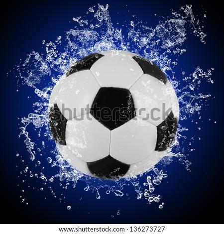 Soccer ball in splashing water - stock photo