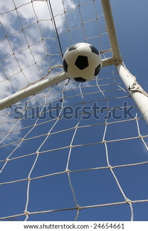 Soccer ball in the goal with room for copy below - stock photo