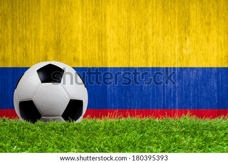 Soccer ball on grass with Colombia flag background close up - stock photo