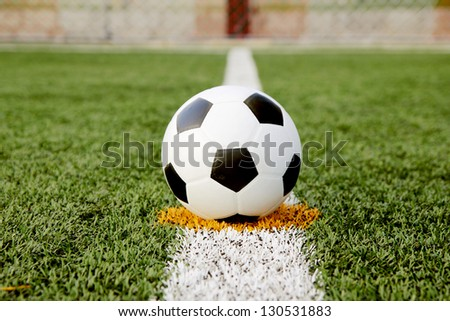 Soccer ball on green grass field with line - stock photo