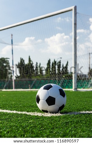 soccer ball on green grass in front of goal net - stock photo