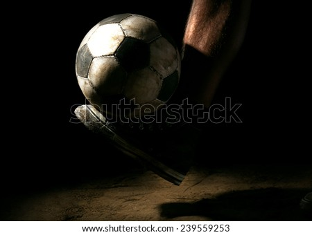 Soccer ball on ground on dark background - stock photo