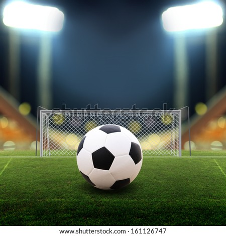 Soccer ball on Soccer field with bright spotlights - stock photo