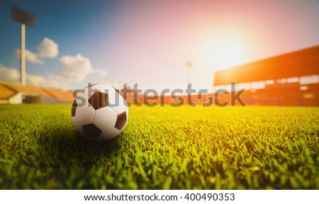 Soccer ball on the grass  grass in soccer stadium , sunset - stock photo