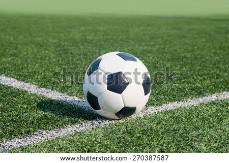 Soccer ball on the lawn green. - stock photo