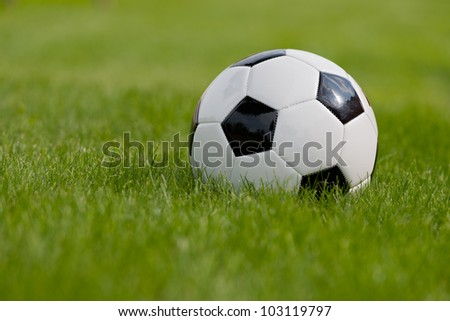 Soccer ball or football ball on green field - stock photo