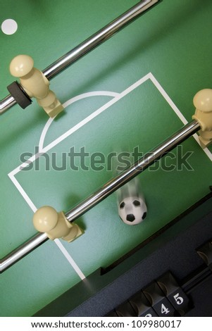 Soccer ball scoring on foosball table - stock photo