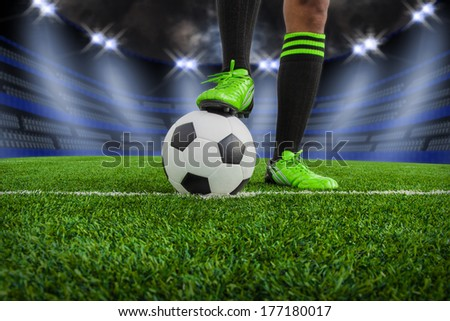 soccer ball with feet player on the football field in stadium at night - stock photo