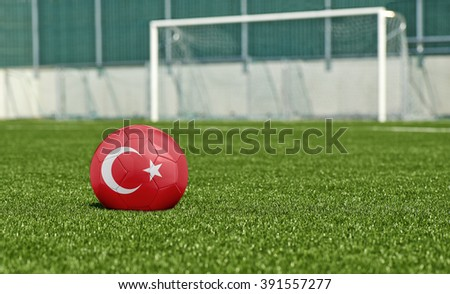 Soccer ball with the flag from Turkey on the green field - stock photo