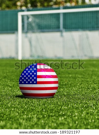 Soccer Ball with USA Flag on the grass in stadium - stock photo