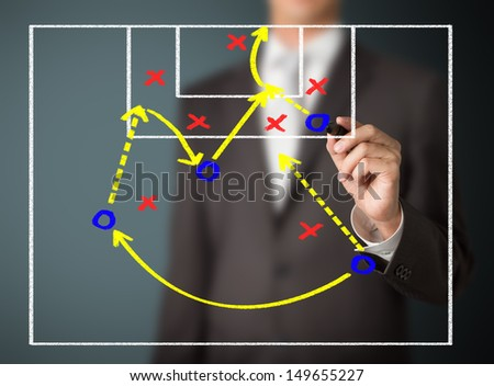 soccer coach writing attacking game strategy - stock photo