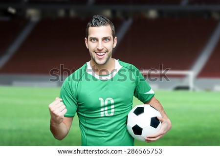 Soccer fan celebrates with green t-shirt on stadium background - stock photo