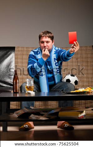 soccer fan is sitting on sofa with beer and showing red card at home - stock photo
