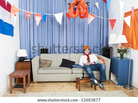 Soccer fan sitting alone in a decorated living room, without any friends to watch the game with him - stock photo