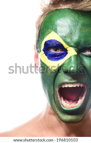 Soccer fan with brazil flag painted over face - stock photo