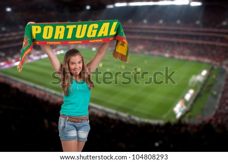 soccer fan with the stadium on the back with a portuguese scarf - stock photo