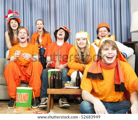 Soccer fans laughing at what's happening during a game of their national team - stock photo