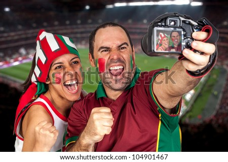 soccer fans taking photo with the stadium on the back with a portuguese scarf - stock photo