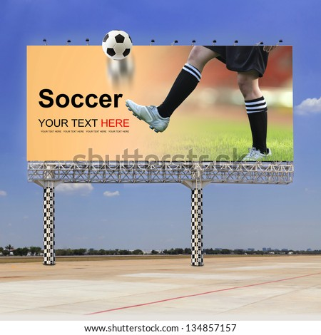 Soccer field, Soccer player on outdoor billboard - stock photo