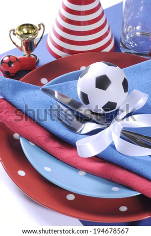 Soccer football celebration party table setting with pates, cutlery, glasses, trophy, soccer ball and decorations in red white and blue team colors - vertical close up. - stock photo