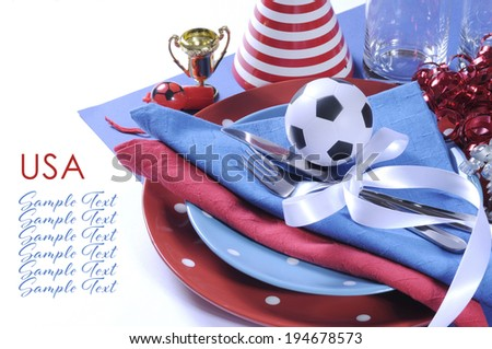 Soccer football celebration party table setting with pates, cutlery, glasses, trophy, soccer ball and decorations in  red white and blue team colors, with copy space. - stock photo