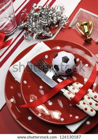 Soccer football celebration party table settings in red and white team colors. Vertical portrait orientation. - stock photo