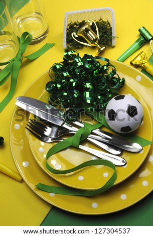 Soccer football celebration party table settings in yellow and green team colors.  Vertical portrait orientation. - stock photo