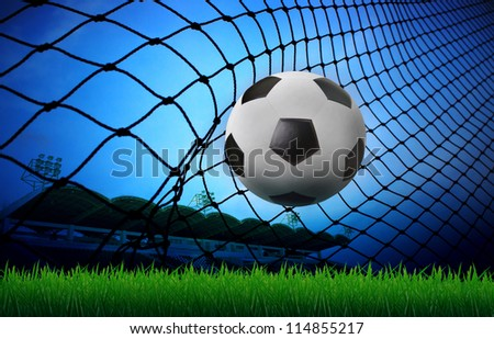 soccer football in goal net and stadium blue sky background - stock photo