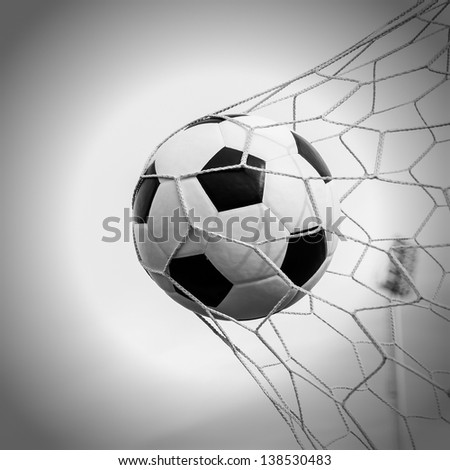 Soccer football in Goal net with Blue sky field. - stock photo