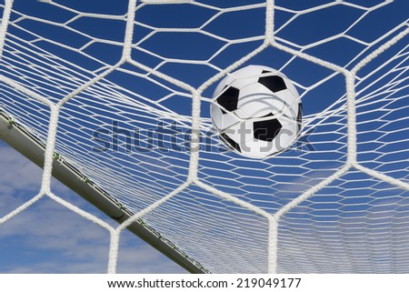 Soccer football in Goal net with sky field. - stock photo
