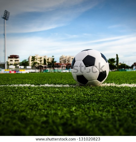 Soccer Football on the green grass of Soccer field with player playing soccer. - stock photo