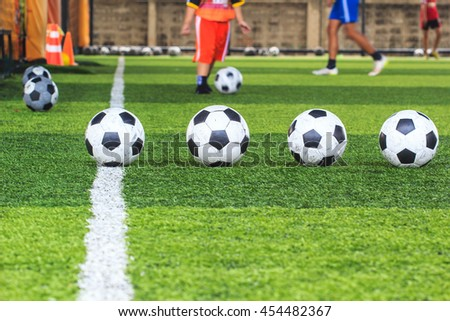 Soccer four ball field football in green grass with background Training children in Soccer academy - stock photo