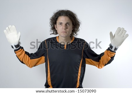 Soccer goalie wearing gloves looks serious as he has his hands out. Horizontally framed photograph. - stock photo