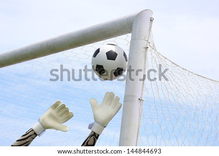Soccer goalkeeper's hands reaching for the ball - stock photo